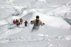 Skiing down the Giants Cascade. A skier being watched by his friends as he skis down through powder snow on the Giant's Cascade on the Mt Blanc, France.  In the Stock Photos