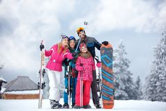 Skiing family enjoying winter vacation on snow in cold day and m. Aking mobile selfie in mountains Stock Photos