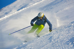 Skiing on fresh snow at winter season. Skier skiing downhill on fresh powder snow  with sun and mountains in background Stock Photos