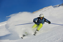 Skiing on fresh snow at winter season sunny day. Skier skiing downhill on fresh powder snow  with sun and mountains in background Stock Photos