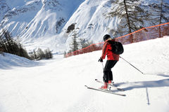 Skiing on fresh snow at winter season at sunny day. Skier skiing downhill on fresh powder snow  with sun and mountains in background Stock Image