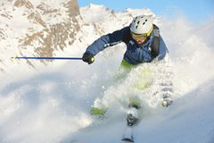 Skiing on fresh snow at winter season at sunny day. Skier skiing downhill on fresh powder snow  with sun and mountains in background Royalty Free Stock Photo