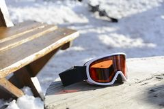 Skiing glasses with orange glass on a wooden table after skiing. stock photo