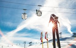 Skiing goggles and skis poles at resort glacier with chair lift. On french alps - Winter vacation travel concept - High season opening on mountain slopes Stock Photos