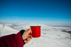After skiing, it is a great pleasure to drink hot coffee from a red mug stock image