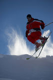 Skiing - jump. Male skier in action with snow being lit from behind Stock Photos