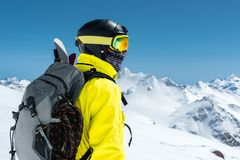Skiing. Portrait of a professional skier at the back view against a background of snow-capped mountains Italian Alps. Europe Stock Photos