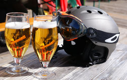Skiing resort. Glasses of beer and a ski helmet. Royalty Free Stock Photos