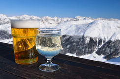 Skiing resort. Glasses with beer and white wine. royalty free stock photos