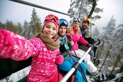 Skiing, ski lift, ski resort - happy family skiers on ski lift m. Skiing, ski lift, ski resort - happy smiling family skiers on ski lift making selfie royalty free stock images