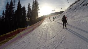 Skiing skiers on the piste in Bukovel ski resort, Ukraine stock video