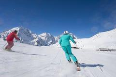 Skiing on skirun in the alps - prepared piste and sunny day. Alpine skiinig near ski lodge Stock Images