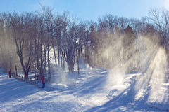 Skiing slope preparation on a sunny winter day. Snow dust over the skiing hill in sunlight Royalty Free Stock Photo