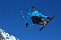 Skiing Stunt. VERBIER, SWITZERLAND - MARCH 3: Freestyle skier performing a rear grab against a blue sky: March 3, 2012 in Verbier, Switzerland royalty free stock photo