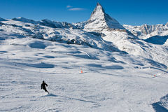 Skiing in the Swiss Alps Alone. A lone skier goes down the mountain with the Matterhorn in the background Stock Photo