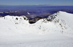 Skiing in Tatra Mountains in Poland. Ski runs and chairlift on Hala Gasienicowa in Tatra mountains in Poland with the far view of Zakopane ski resort and Podhale stock photos