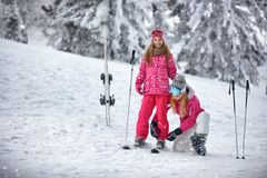Skiing, winter, snow, sun and fun - Mother preparing for skiing. Happy daughter Royalty Free Stock Photo