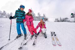 Skiing, winter, snow, sun and fun - mother preparing for skiing stock image