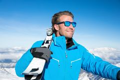 Skiing in the winter snowy mountains. Young, sexy man is skiing in winter paradise in the alps with a beautiful blue sky and wonderful white snowy mountains Stock Photography