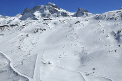Skiing in Zermatt. Ski runs in the swiss ski resort of Zermatt with the peak of the breithorn and the kleine matterhorn (right) in the background Royalty Free Stock Photos