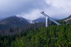 Skijump in-run tower in Tatry mountains. A ski jump in-run tower protruding out of a forest near the lake named Strbske pleso in Tatry mountains, Slovakia stock photos