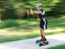 Skiking. Athlete skiking in the woods, shot from the side Royalty Free Stock Photos