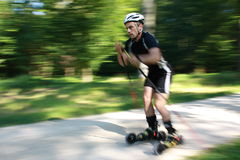 Skiking. Athlete skiking in the woods, shot from the side Stock Images