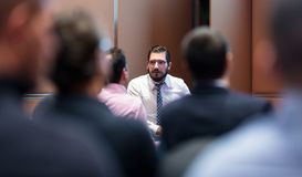 Skiled Businessman Presenting a Project to His Work Team atl Company Meeting. Skiled businessman presenting project to his work team at informal company Stock Photos