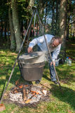 Skilful cook prepares soup over the fire Stock Photos