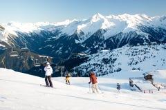 Skilift en skihelling met skiërs onder het op zonnige de winterdag met blauwe hemel stock afbeelding