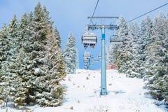 Skilift met skiërs bij skitoevlucht Stock Foto's