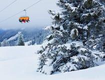Skilift met skiërs bij skitoevlucht Stock Afbeeldingen
