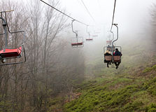 Skilift trägt Touristen zum nebelhaften Berg lizenzfreie stockbilder