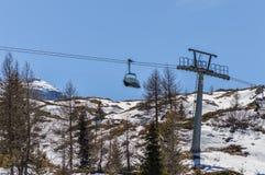 Skilift tussen pijnboombomen op de Dolomietbergen dichtbij Trento in Italië Stock Afbeelding