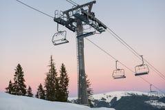 Skiliftstoelen bij de de wintertoevlucht tegen hemel bij zonsondergang stock foto
