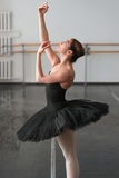 Skill ballerina posing in ballet class. Barrre and white wall on background Stock Photos
