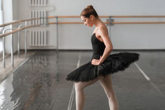 Skill ballerina posing in ballet class. Barrre and white wall on background Stock Image