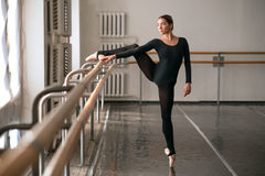 Skill ballerina posing in ballet class. Barrre and white wall on background Royalty Free Stock Image
