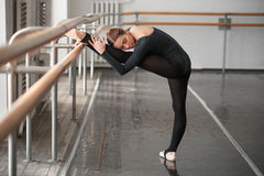 Skill ballet dancer posing in class. Barrre and white wall on background Stock Photos