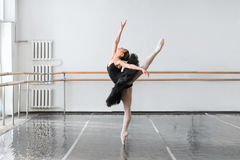 Skill ballet dancer shows stretching in class. Skill female ballet dancer shows stretching in class, barrre and white wall on background Royalty Free Stock Image