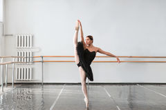 Skill ballet dancer shows stretching in class. Skill female ballet dancer shows stretching in class, barrre and white wall on background stock photo