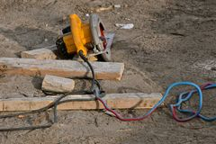Skill saw left on ground at a construction site. A skill saw hooked up to a heavy electrical cord is left on the ground at a construction site stock image
