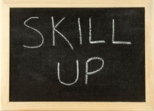 Skill up. The words 'SKILL UP' hand written in white chalk on a black board with a wooden frame Royalty Free Stock Image