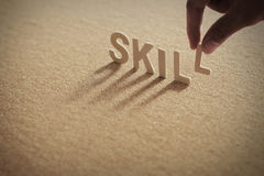 SKILL wood word on compressed board. With human`s finger at L letter Stock Photography