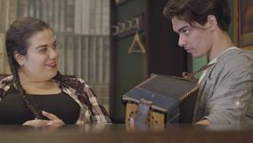 Skill young man playing the accordion for a cute fat girl with a pigtail. Cheerful music on the old instrument. Folk. Concept stock video footage