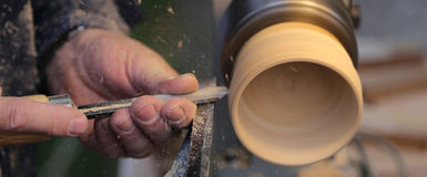 Skilled artisan during the work of the wooden piece with the lat. He in the carpentry royalty free stock images