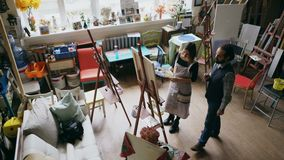 Skilled artist man teaching young woman painting on easel at art school studio - creativity, education and art people stock footage
