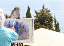 Skilled artist painting nature on easel outdoors. Skilled artist painting nature with brush on easel, outdoors, inspired by a scenic landscape with tall green Royalty Free Stock Photos