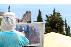 Skilled artist painting nature on easel outdoors. Skilled artist painting nature with brush on easel, outdoors, inspired by a scenic landscape with tall green Stock Photography