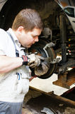 Skilled auto mechanic. A closeup of an auto mechanic concentrating as he fixes a car Royalty Free Stock Photo